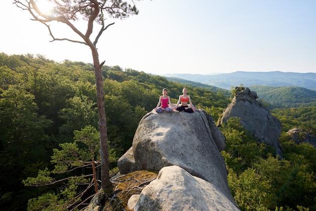 Dwie Atrakcyjne Dziewczyny Siedzą Medytując W Lotosowej Pozie, Oświetlone Letnim Słońcem, Na Szczycie Wielkiej Skały W Górskim Lesie Premium Zdjęcia