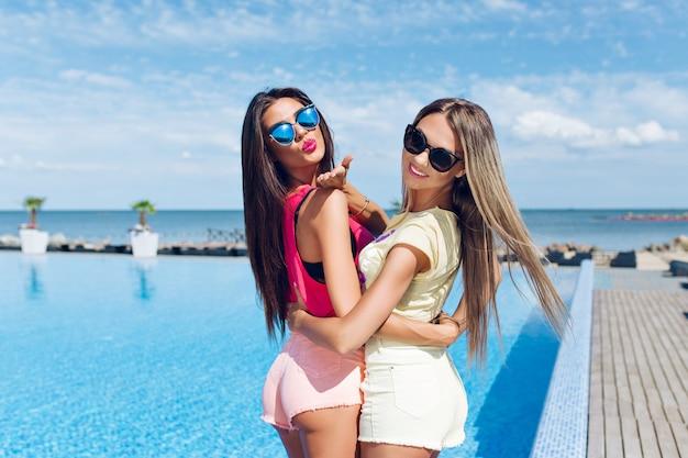 Dwie Atrakcyjne Dziewczyny W Okularach Przeciwsłonecznych Z Długimi Włosami W Pobliżu Basenu Na Słońcu. Widok Z Tyłu. Darmowe Zdjęcia