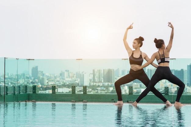 Dwie atrakcyjne kobiety grają jogę. przy basenie dla jej dobrego zdrowia Premium Zdjęcia