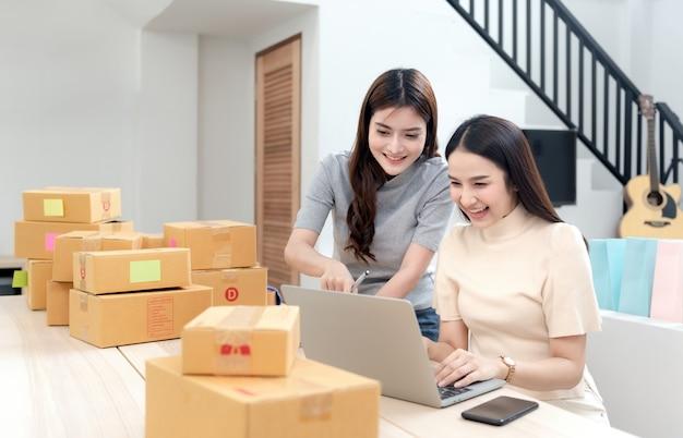 Dwie Azjatki Patrzą Na Swoje Laptopy, Aby Sprawdzić Zamówienia, A Dookoła Są Kartonowe Pudełka I Torby Na Zakupy Premium Zdjęcia