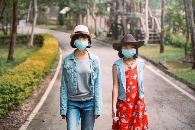 Dwie Azjatki Podróżują W Ochronie Twarzy W Celu Zapobiegania Koronawirusowi Podczas Spacerowania W Parku Premium Zdjęcia