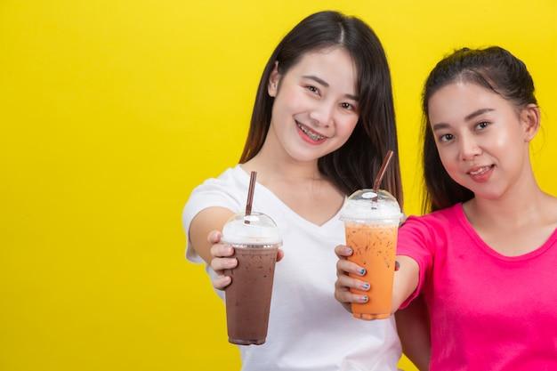 Dwie azjatyckie kobiety piją mrożoną herbatę mleczną i mrożoną kakao na żółtym. Darmowe Zdjęcia
