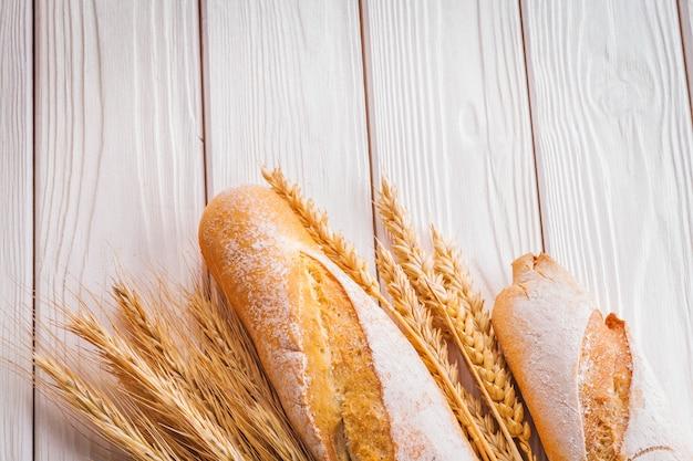 Dwie Bagietki I Kłosy Pszenicy Na Białych Tablicach Malowanych Koncepcja Jedzenia I Picia Premium Zdjęcia