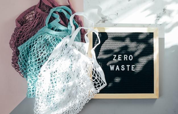 Dwie bawełniane torby wielokrotnego użytku (torby siatkowe) i czarna tablica z napisem zero waste on Premium Zdjęcia