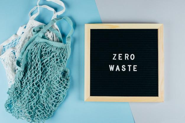 Dwie bawełniane torby wielokrotnego użytku (torby siatkowe) i tablica z tekstem zero waste Premium Zdjęcia