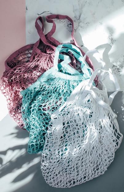 Dwie bawełniane torby wielokrotnego użytku (torby siatkowe) w trójkolorowym kolorze z cieniami. przyjazny dla środowiska Premium Zdjęcia