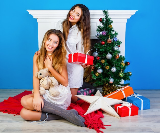 Dwie Całkiem Najlepsze Przyjaciółki Otwierają Prezenty świąteczne Przy Kominku I Udekorują Choinkę Noworoczną. Wspólna Zabawa Podczas Ferii Zimowych. Darmowe Zdjęcia