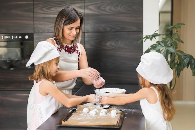 Dwie córki i matka przygotowanie cookie na blacie kuchennym Darmowe Zdjęcia