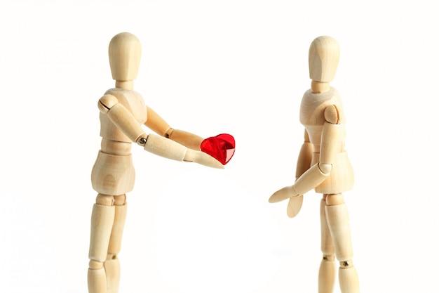 Dwie Drewniane Figurki Manekina, Dają Czerwone Serce, Odizolowane Na Białej Powierzchni - Zdjęcia Motywów Koncepcyjnych Miłość I Walentynki Premium Zdjęcia