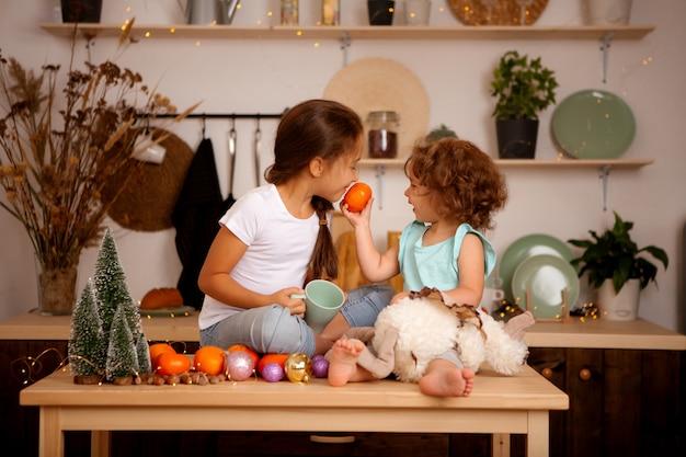 Dwie Dziewczynki Jedzące Mandarynki W świątecznej Kuchni Premium Zdjęcia