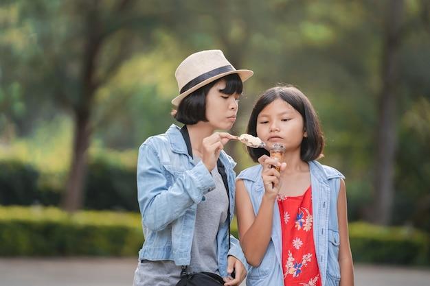 Dwie Dziewczyny Jedzenie Lodów Na Ulicy Podczas Spaceru W Parku Premium Zdjęcia