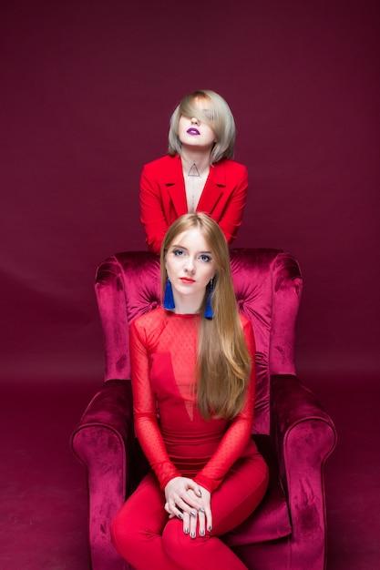Dwie Dziewczyny Kobieta W Czerwone Ubrania Lokalizacji Czerwone Krzesło I Czerwonym Tle Premium Zdjęcia