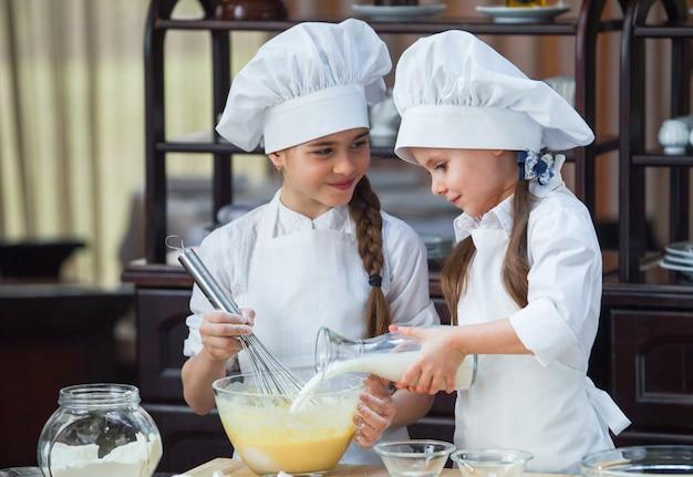 Dwie dziewczyny robią ciasto na mąkę. Premium Zdjęcia