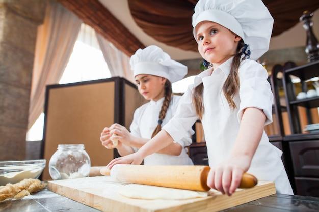 Dwie Dziewczyny Robią Ciasto Z Mąki. Premium Zdjęcia