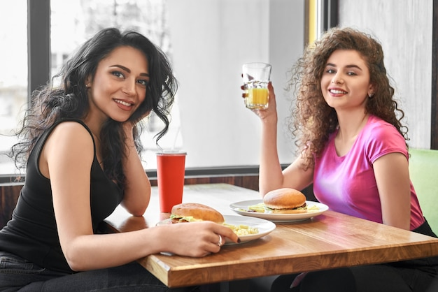 Dwie Dziewczyny Siedzą W Kawiarni W Pobliżu Okna, Jedząc Fast Food. Premium Zdjęcia