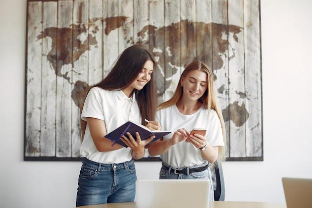 Dwie Dziewczyny W Białych Koszulkach Pracujących W Biurze Darmowe Zdjęcia