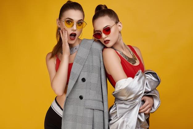 Dwie eleganckie glamour hipster bliźniaczki w modnym czerwonym topie, czarnych szortach Premium Zdjęcia
