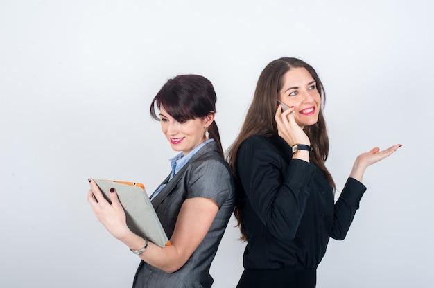 Dwie kobiety biznesu stojące plecami do siebie i uśmiechnięte Premium Zdjęcia