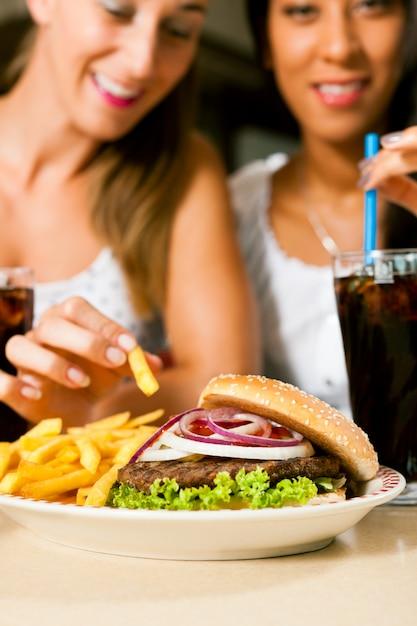 Dwie kobiety je hamburgera i pije sodę Premium Zdjęcia