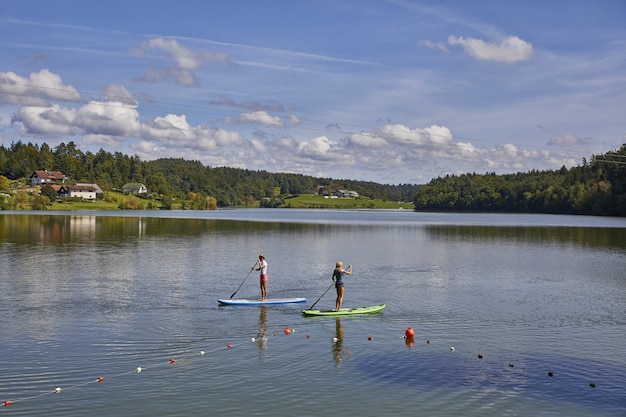 Dwie Kobiety Na Desce Do Wiosłowania Na Stojąco W Jeziorze Smartinsko W Słowenii Darmowe Zdjęcia