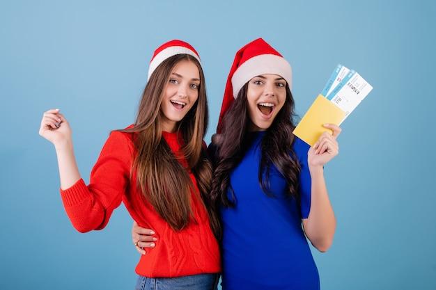 Dwie kobiety noszące czapki mikołaja z biletami i paszportem odizolowane na niebiesko Premium Zdjęcia