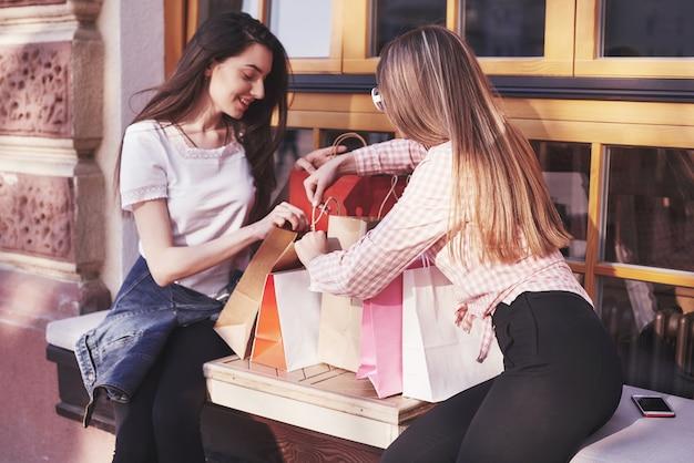 Dwie Kobiety Rozmawiają Po Zakupach Na Ulicy W Pobliżu Okna. Darmowe Zdjęcia
