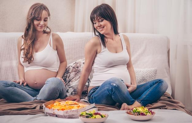 Dwie Kobiety W Ciąży Jedzące Pizzę I Sałatkę W Domu Premium Zdjęcia