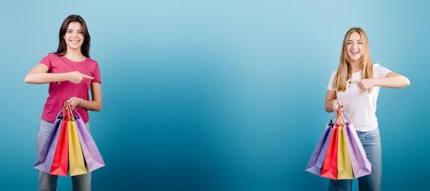 Dwie Kobiety Z Palcami Kolorowe Torby Na Zakupy, Wskazując Palcami Na Przestrzeni Między Nimi Na Niebiesko Premium Zdjęcia