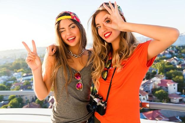 Dwie ładne Przyjaciółki, Wesołe Dziewczyny, Które Bawią Się I Robią śmieszne, Szalone Miny Na Dachu Darmowe Zdjęcia