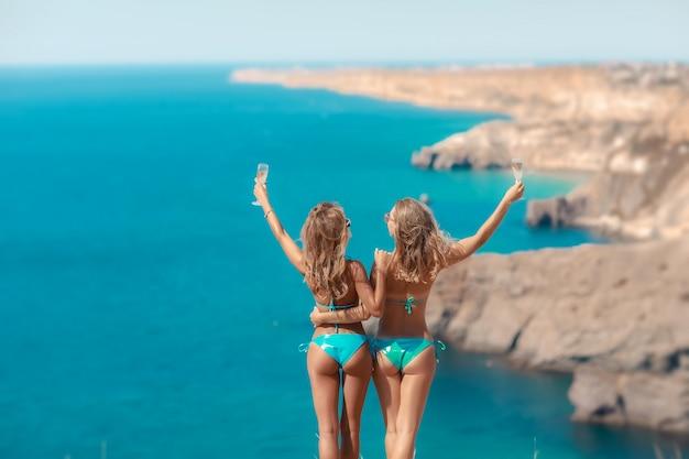 Dwie Letnie Dziewczyny W Bikini Strojach Kąpielowych Stoją Ramię W Ramię Na Górze Nad Morzem Premium Zdjęcia