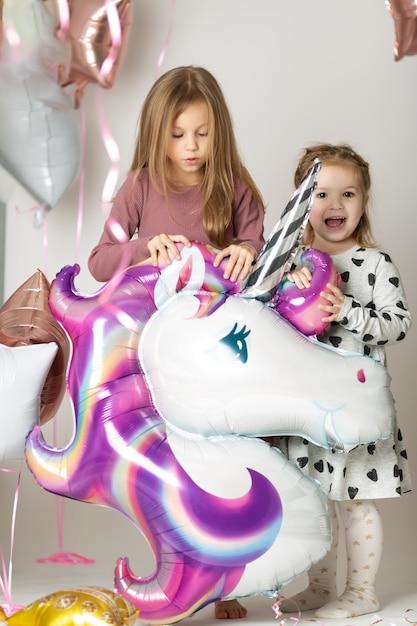 Dwie Małe Dziewczynki Bawią Się Dużym Balonem Jednorożca Otoczonym Balonami Premium Zdjęcia