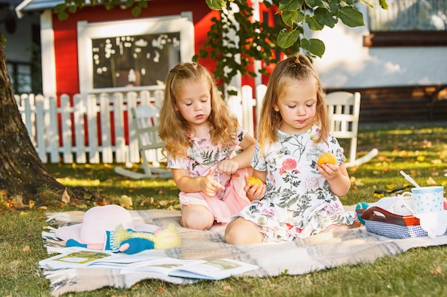 Dwie Małe Dziewczynki Siedzi Na Zielonej Trawie Darmowe Zdjęcia