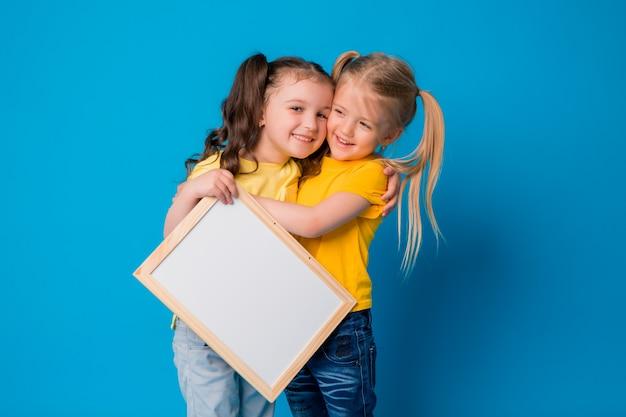 Dwie małe dziewczynki uśmiechnięte z pustą deską kreślarską na niebieskim tle Premium Zdjęcia