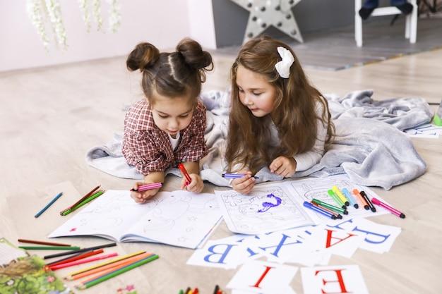 Dwie Małe Urocze Dziewczynki, Które Rysują W Kolorowance Leżącej Na Podłodze Na Kocu I Uczą Się Liter Darmowe Zdjęcia
