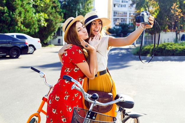 Dwie Młode Całkiem Stylowe Dziewczyny Pozują W Pobliżu Jasnych Retro Rowerów Hipster I Autoportret Darmowe Zdjęcia