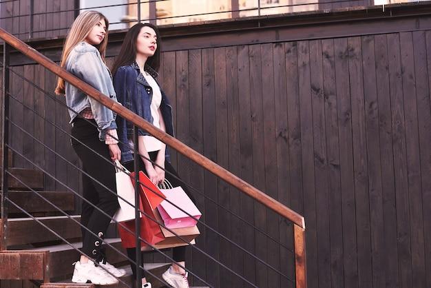 Dwie Młode Kobiety Niosące Torby Na Zakupy Idąc Po Schodach Po Wizycie W Sklepach. Darmowe Zdjęcia