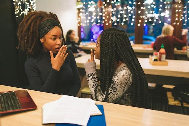 Dwie Młode Kobiety Plotkują Przy Stole Premium Zdjęcia