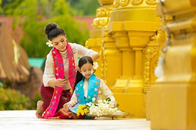Dwie młode kobiety w birmańskich strojach ludowych pomagają układać kwiaty, oferując mnichom ważne daty buddyjskie. Premium Zdjęcia