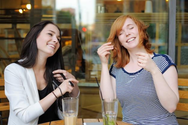 Dwie Młode Kobiety Zabawy W Kawiarni Na świeżym Powietrzu Premium Zdjęcia