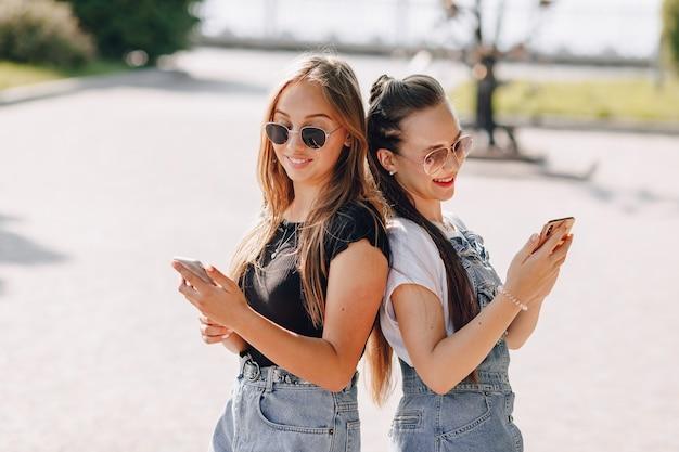 Dwie Młode ładne Dziewczyny Na Spacerze W Parku Z Telefonami Darmowe Zdjęcia