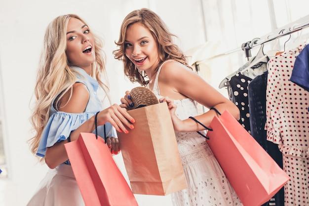 Dwie Młode ładne Dziewczyny Oglądające Sukienki I Przymierzające Je, Wybierając W Sklepie Darmowe Zdjęcia