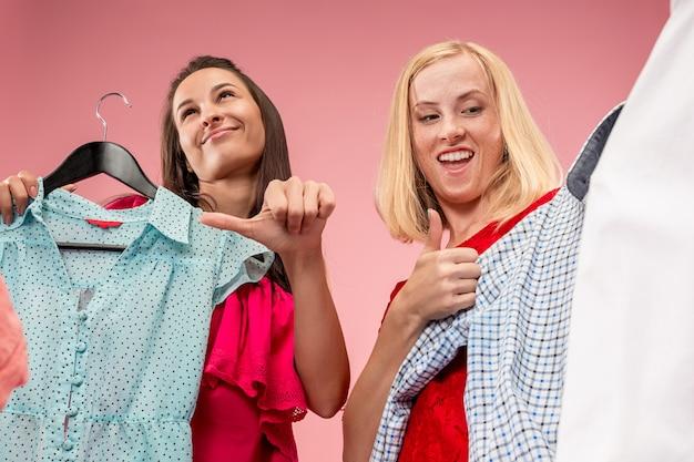 Dwie Młode ładne Dziewczyny Patrzą Na Sukienki I Przymierzają Je, Wybierając W Sklepie Darmowe Zdjęcia