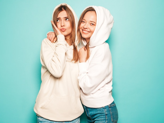 Dwie Młode Piękne Blond Uśmiechnięte Dziewczyny Hipster W Modne Letnie Ubrania Z Kapturem. Seksowne Beztroskie Kobiety Pozuje Blisko Błękit ściany. Modne I Pozytywne Modele Zabawy Darmowe Zdjęcia