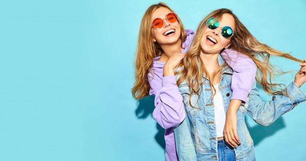 Dwie Młode Piękne Blond Uśmiechnięte Kobiety Hipster W Modne Letnie Ubrania. Seksowne Beztroskie Kobiety Pozuje Blisko Błękit ściany W Okularach Przeciwsłonecznych. Pozytywne Modele Darmowe Zdjęcia