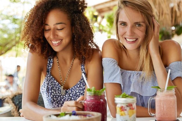 Dwie Młode, Przyjacielskie Suczki Ubrane W Letnie Stroje Pozytywnie Się Uśmiechają, Jedzą Egzotyczne Desery I Piją Smoothie, Cieszą Się Chwilą Wypoczynku Na Tarasie Kawiarnianym Wnętrzu, Będąc W Dobrym Nastroju. Darmowe Zdjęcia