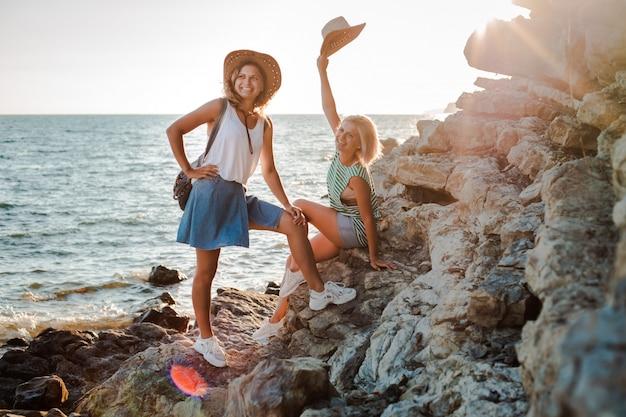 Dwie Młode Rozochocone Kobiety W Modnisiów Kapeluszach Na Skale Na Wybrzeżu Morza. Letni Krajobraz Z Dziewczyną, Morzem, Wyspami I Pomarańczowym światłem Słonecznym. Premium Zdjęcia