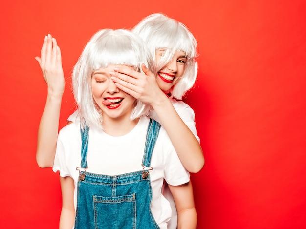 Dwie Młode Seksowne Uśmiechnięte Dziewczyny Hipster W Białe Peruki I Czerwone Usta. Piękne Modne Kobiety W Letnie Ubrania. Modele Pozowanie W Pobliżu Czerwonej ściany W Studio. Zasłonić Oczy Dłońmi Do Swojej Przyjaciółki. Koncepcja Niespodzianka Darmowe Zdjęcia