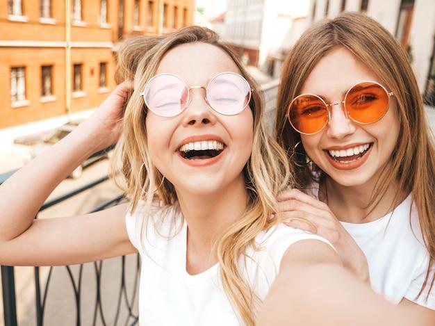 Dwie Młode Uśmiechnięte Hipster Blond Kobiety W Letnie Białe Ubrania Ubrania. Dziewczyny Robienia Zdjęć Autoportretów Selfie Na Smartfonie. . Darmowe Zdjęcia
