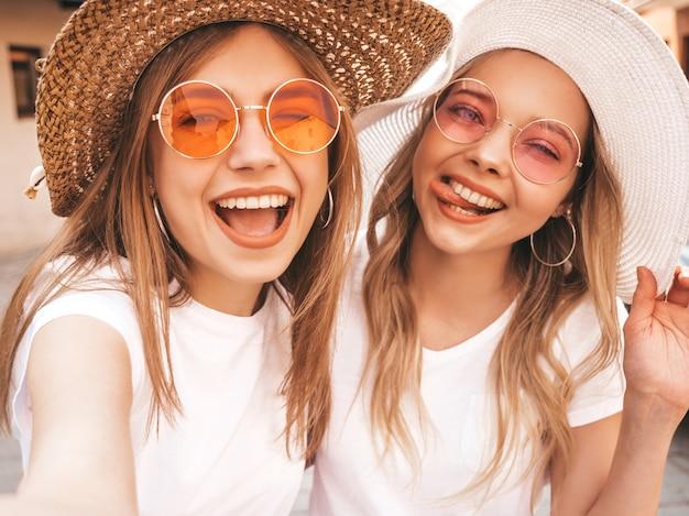 Dwie Młode Uśmiechnięte Hipster Blond Kobiety W Letniej Białej Koszulce. Dziewczyny, Biorąc Selfie Autoportret Zdjęcia Na Smartfonie. Modele Pozowanie Na Tle Ulicy. Kobieta Pokazuje Język I Pozytywne Emocje Darmowe Zdjęcia