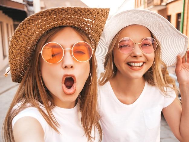 Dwie Młode Uśmiechnięte Hipster Blond Kobiety W Letniej Białej Koszulce. Dziewczyny, Robiąc Selfie Autoportret Zdjęcia Na Smartfonie. Modele Pozowanie Na Tle Ulicy. Kobieta Pokazuje Pozytywne Emocje Darmowe Zdjęcia